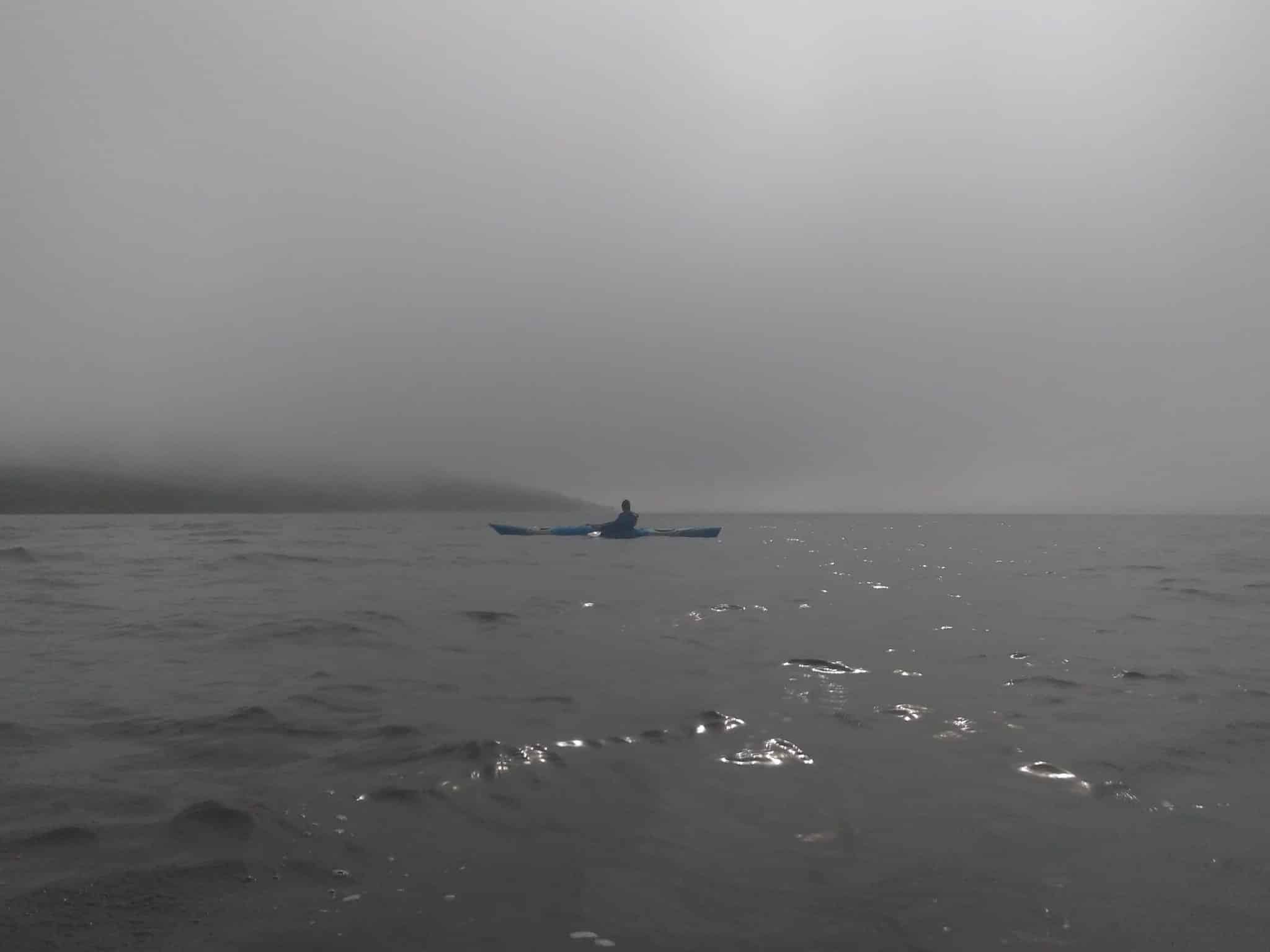 A lone kayaker surrounded by fog in North Iceland.