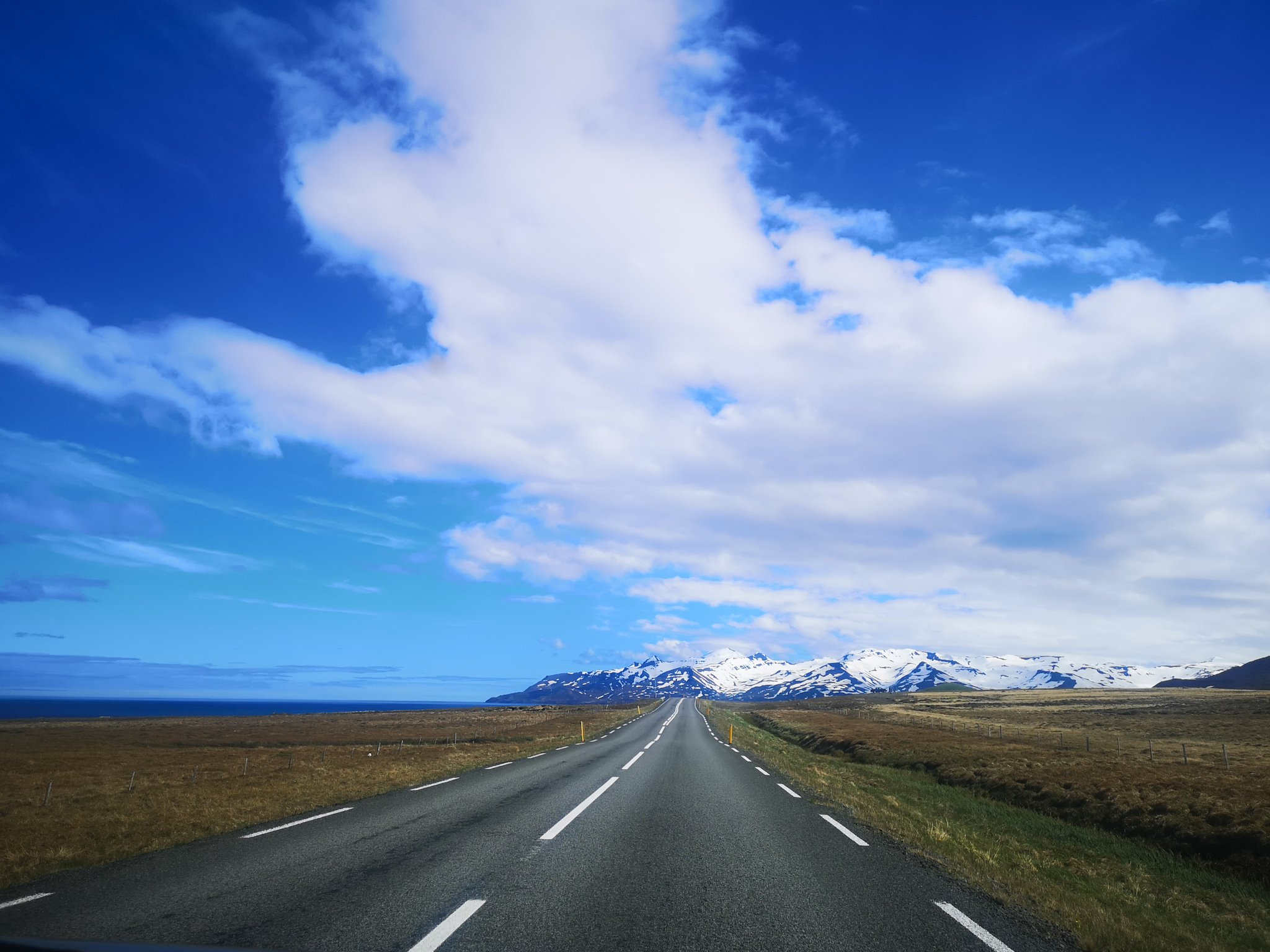 Road in North Iceland with blue sky and mountains in the distance.