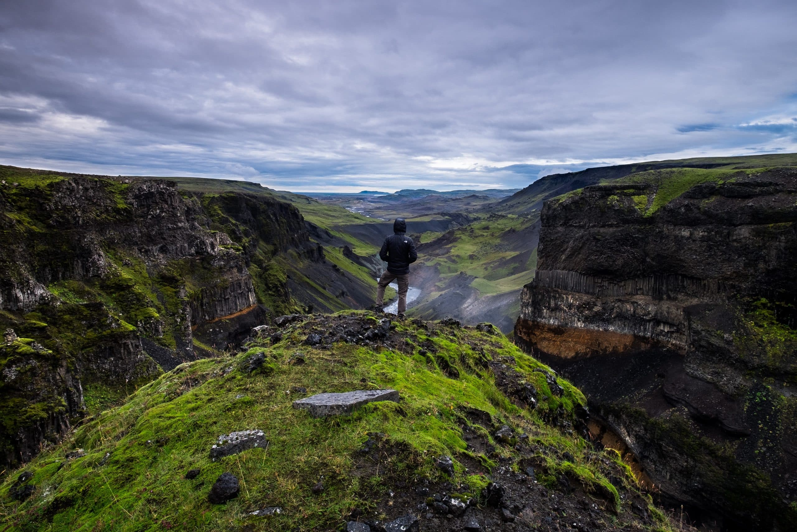 A person standing on a cliff overlooking a canyon in South Iceland.