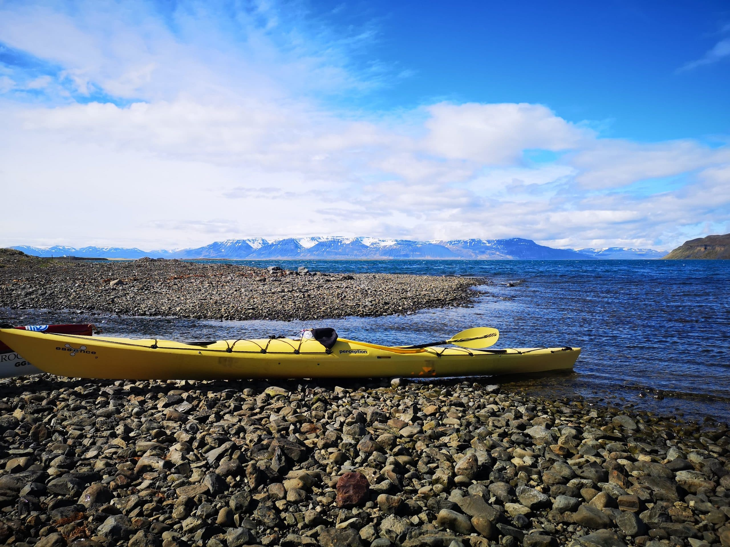 A view of a kayak on a beach, North Iceland's mountains in the background.