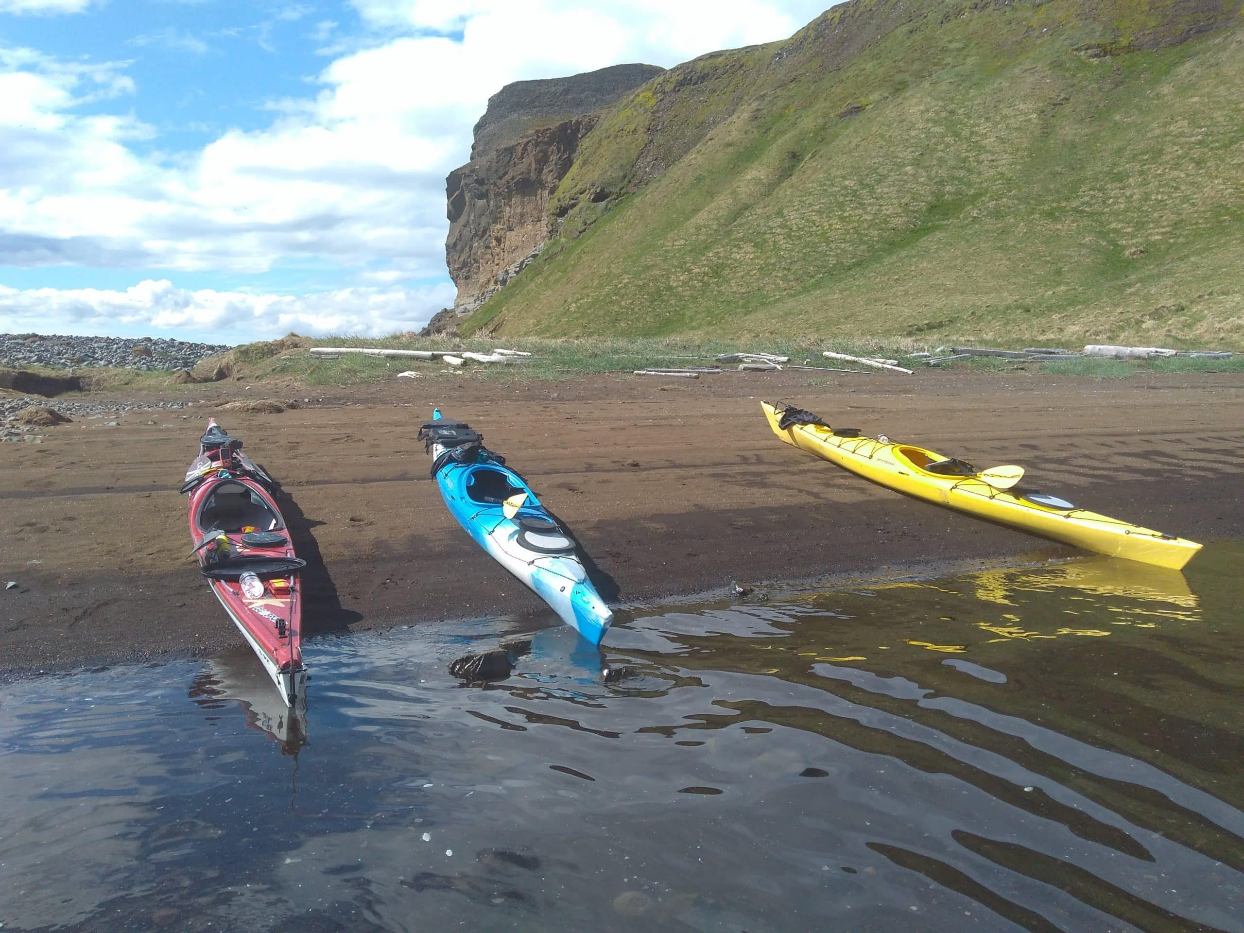Three kayaks on a beach in North Iceland, a green cliff in the background.