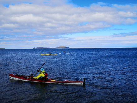 Trois kayakistes sur l'océan bleu au nord de l'Islande.