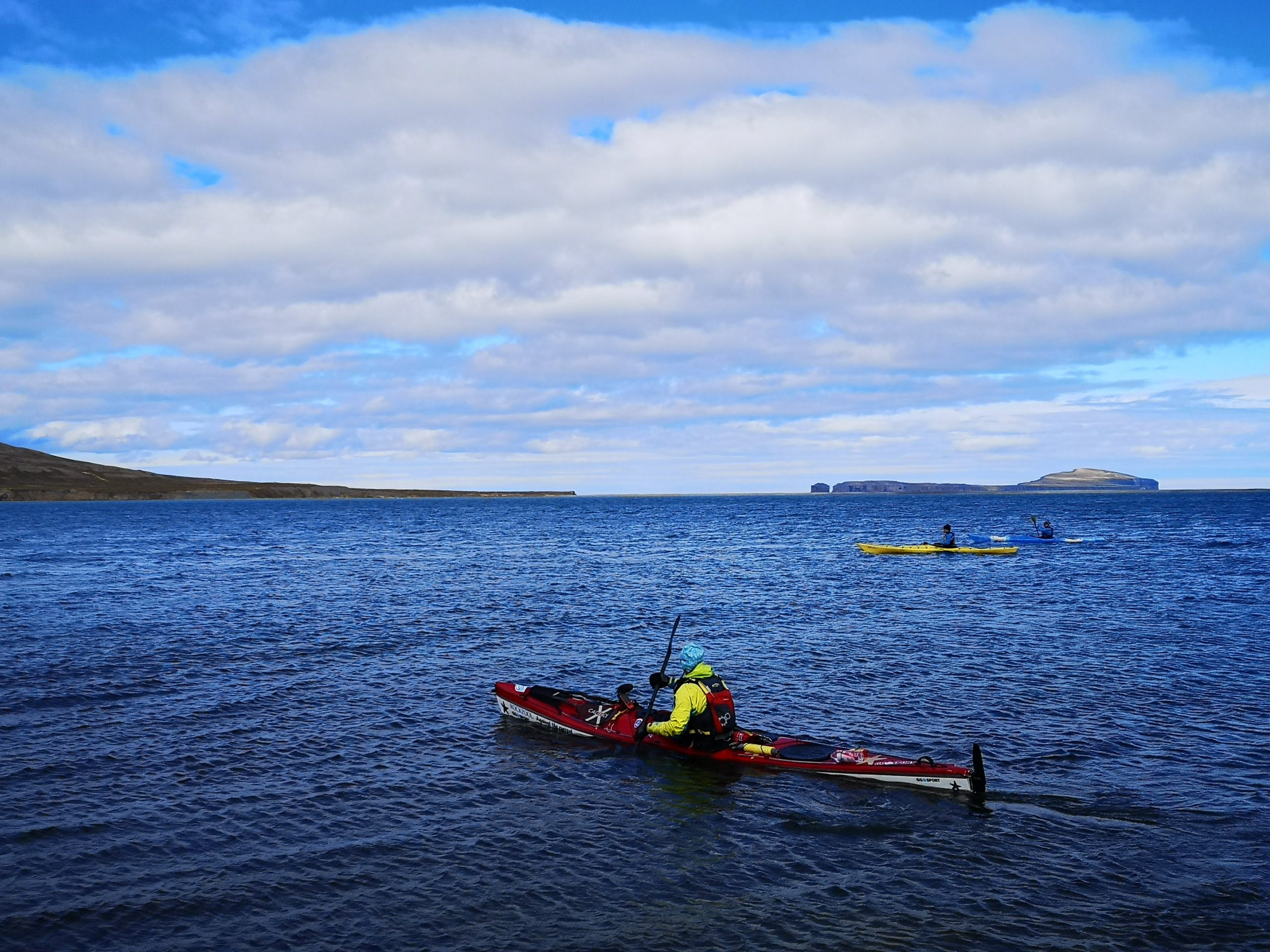 Three kayakers in blue water in North Iceland.