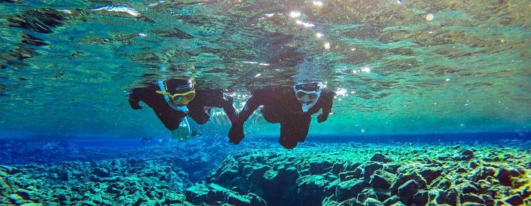 2 snorkelers holding hands in Silfra