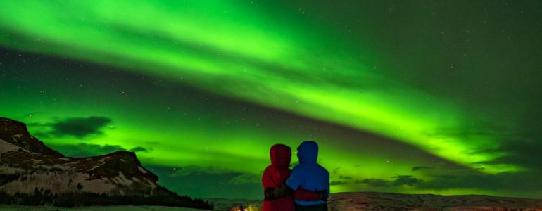 The Northern Lights shine over a travelling couple