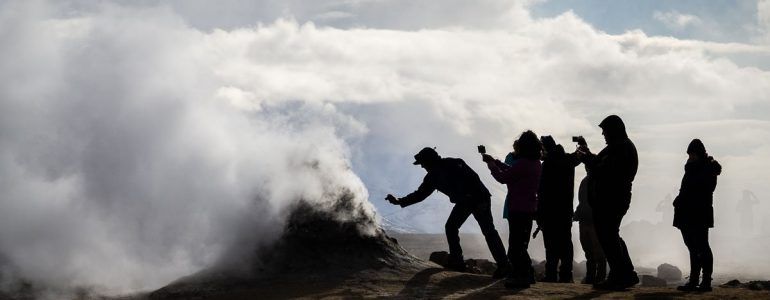 Group of people taking pictures of a a fumarole in northern Iceland