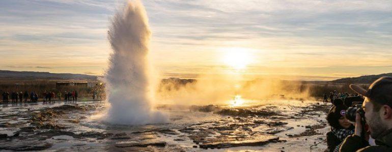 Erupting Strokkur geyser at sunset